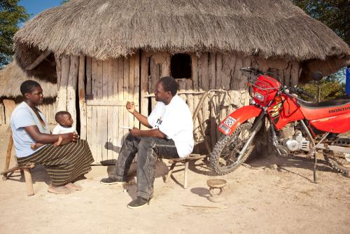 Man, Woman and Child Outside Hut with Motorbike